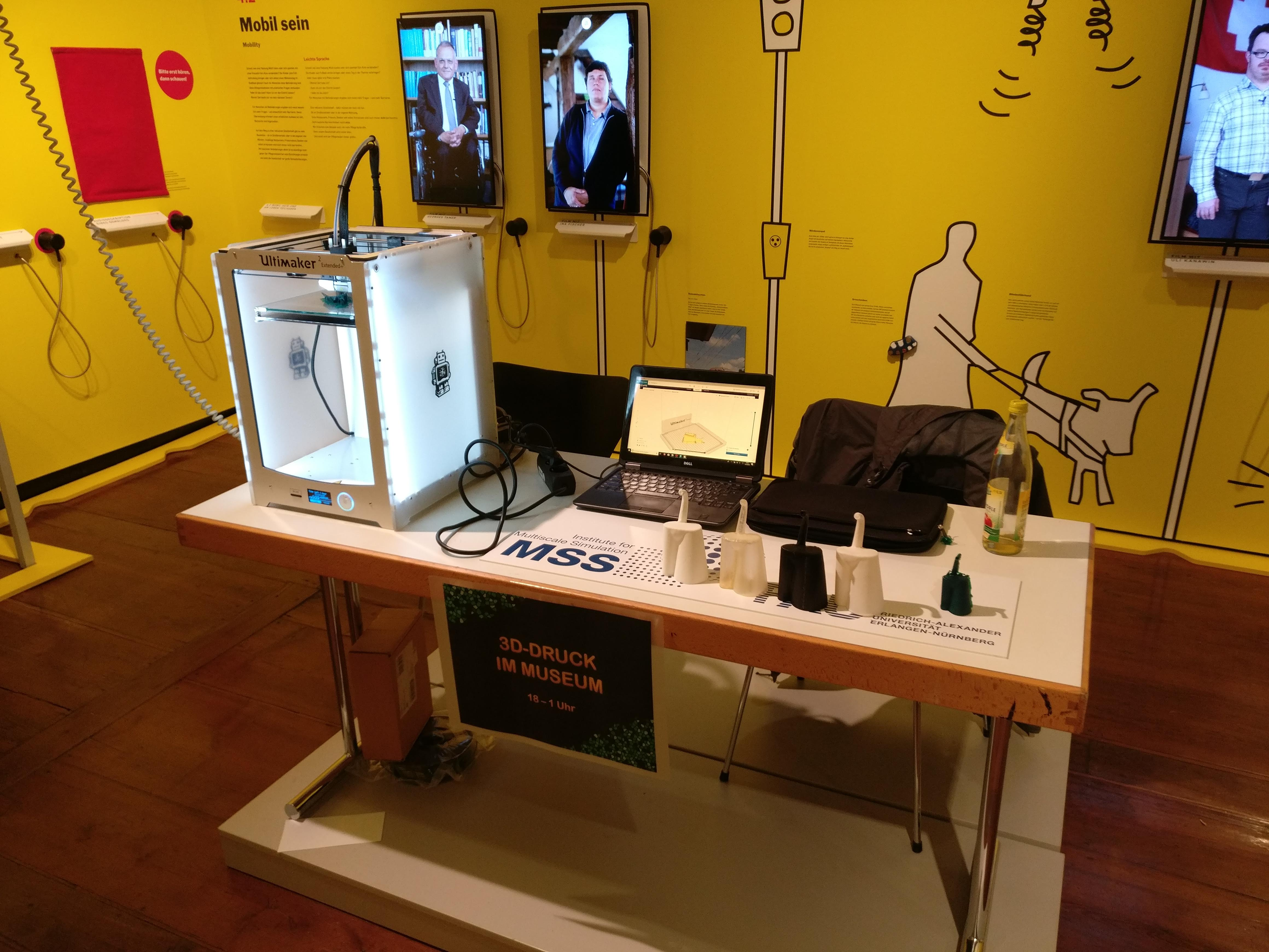 Unser Stand in der Langen Nacht der Wissenschaften 2019. 3D-Drucker und Testmodelle liegen auf dem Tisch.