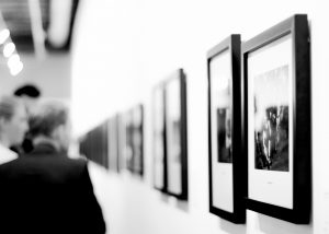 Personen schauen sich Bilder in einer Austellung an. Schwarz-Weiß