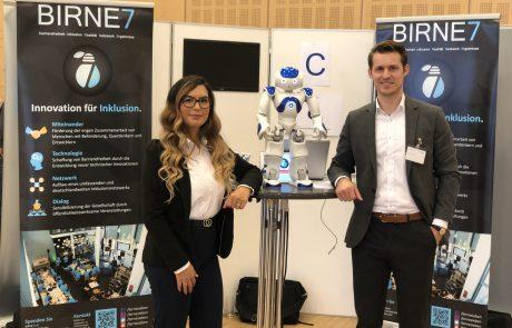"""Zwei Vorstandsmitglieder unseres Vereins stehen am Stand mit dem humanoiden Roboter namens """"Nao"""""""