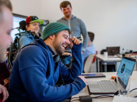 Jonas Jung sitzt lachend vor dem Laptop